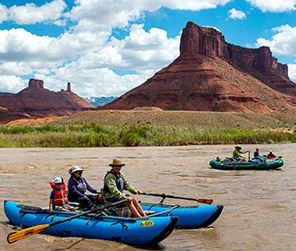 peoples in canoes with the moab mountains in the background